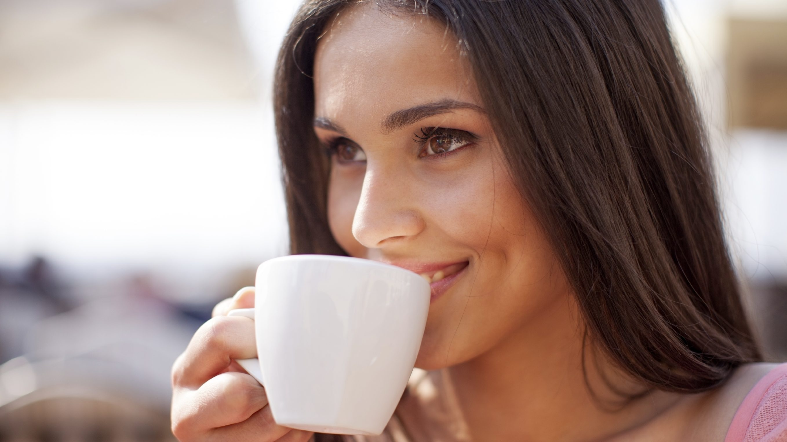 woman with brown hair drinking a cup of coffee from a white mug